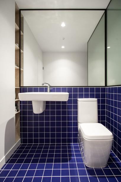 Banheiro com piso e meia parede de azulejos azuis escuros