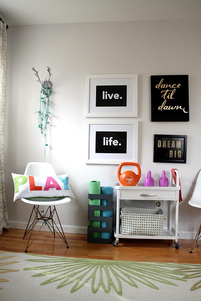 """Sala com uma cadeira com almofada escrito """"play, quadros pendurados na parede; dois tapetes de yoga presos e enconstados contra a parde e um móvel vazado embaixo e com uma gaveta, com alteres em cima dela"""