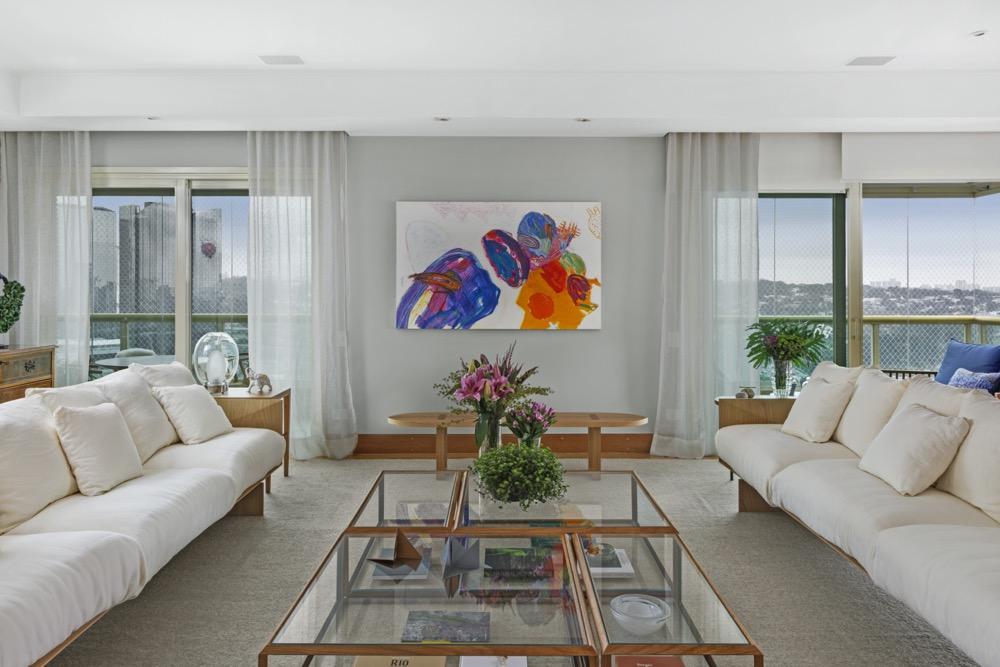 Sala integrada com sofás claros e quadro colorido na parede