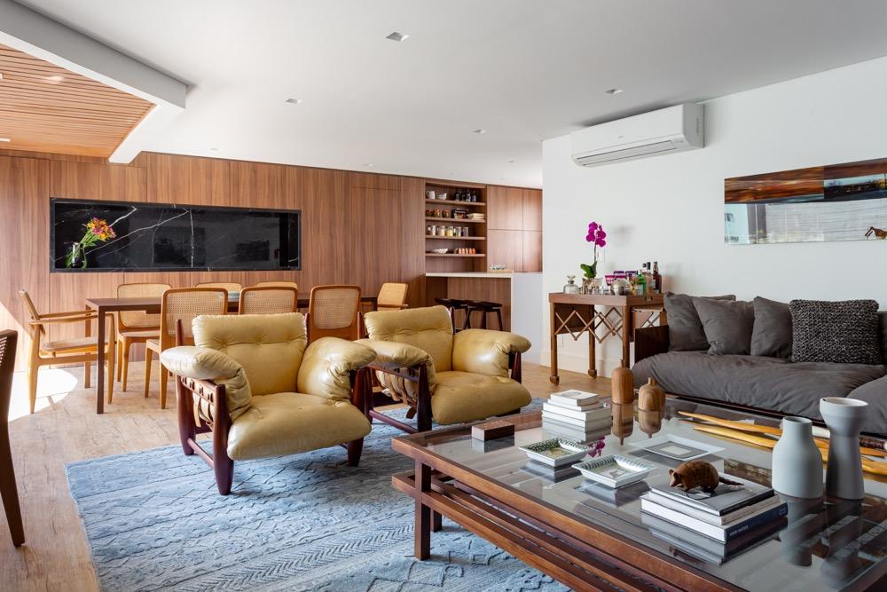 sala integrada com poltrona de couro e painel de madeira