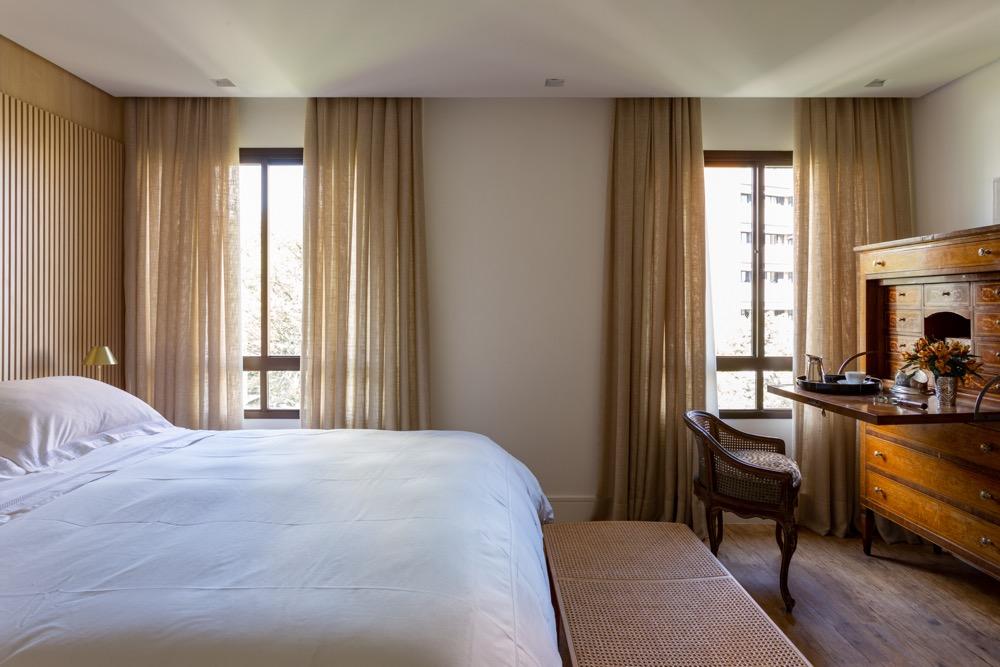 quarto com cortinas leves, madeira e móvel antigo