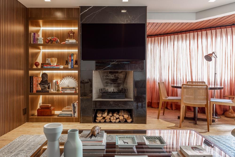 sala com lareira e prateleiras de madeira