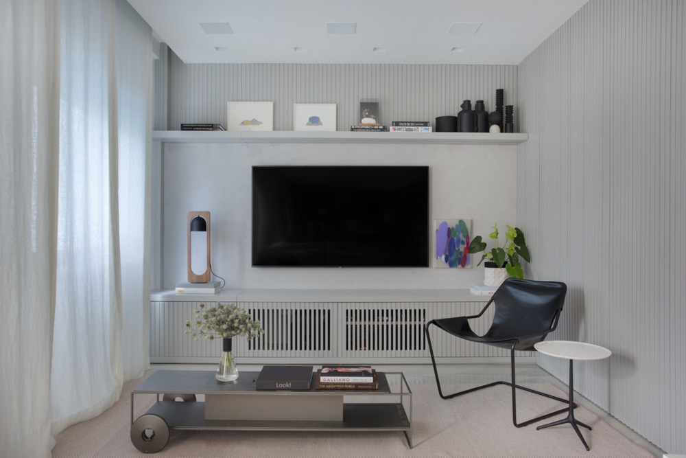sala de estar com cores neutras e painel de TV