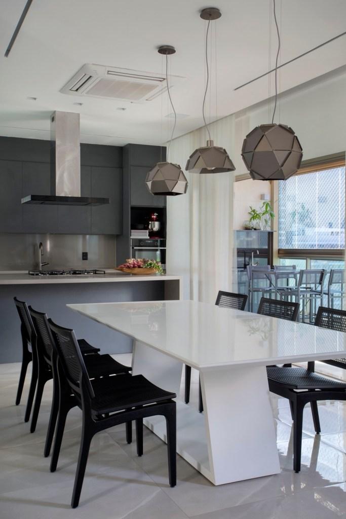 cozinha gourmet com mesa branca e cadeiras pretas