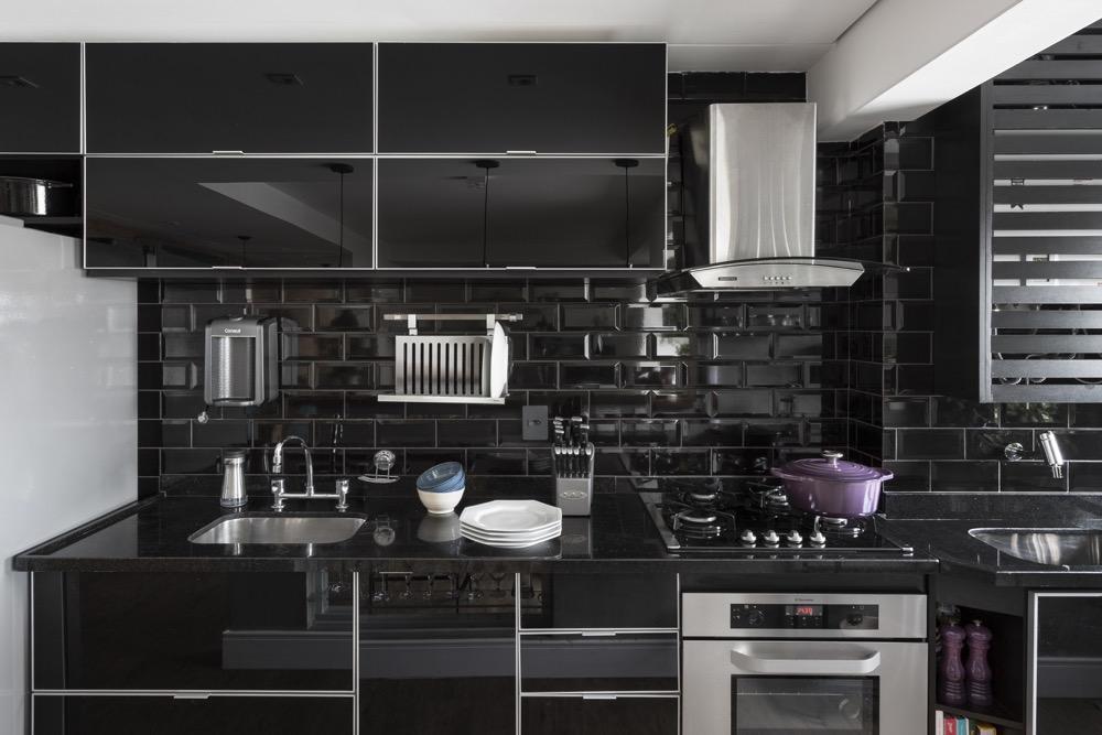 Cozinha com armários e revestimentos pretos
