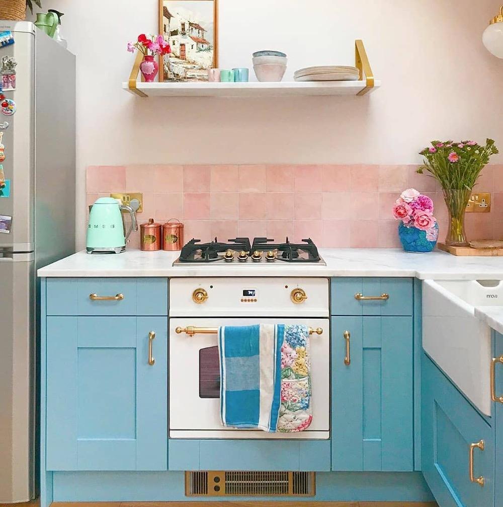 Cozinha com armários azuis e azulejo rosa