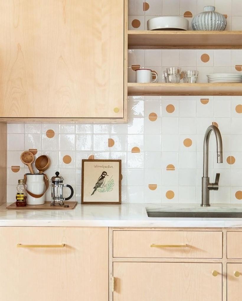 Cozinha com armários de madeira clara e azulejo de bolinhas