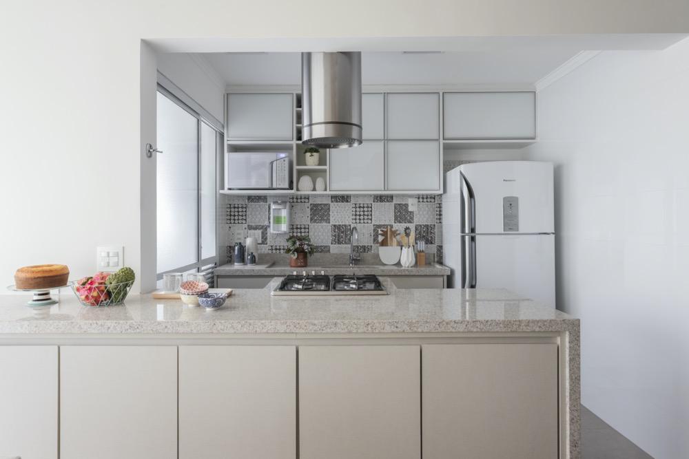 Cozinha com armários de madeira clara e azulejos cinza