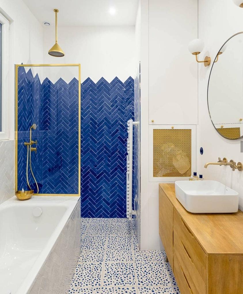 banheiro com revestimentos azuis e metais dourados