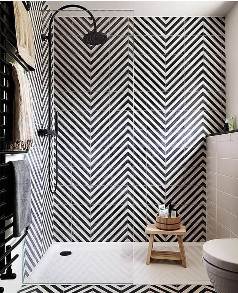 banheiro com revestimento em preto e branco