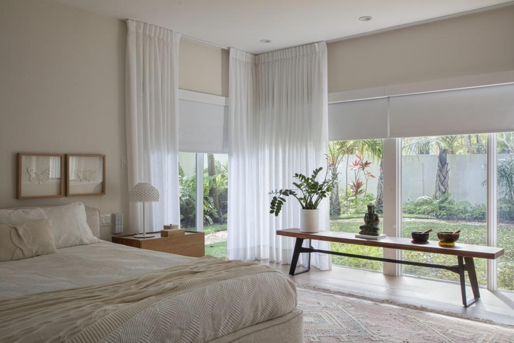 quarto com amplas janelas e decoração de cores claras
