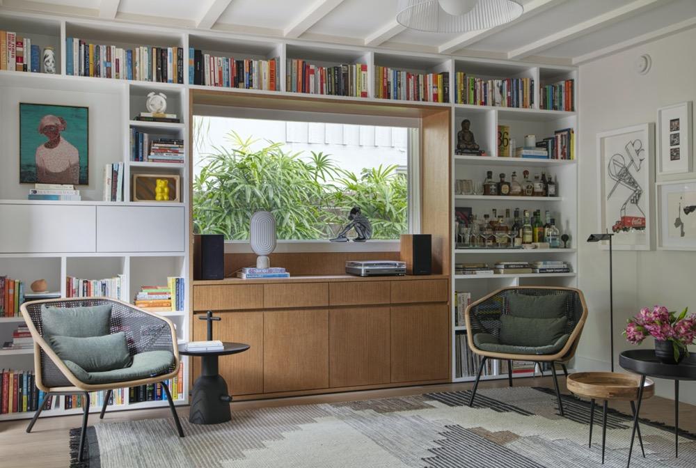 estante de livros com duas poltronas