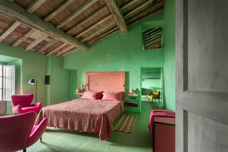 quarto com parede verde e cama rosa