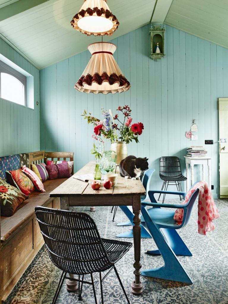 Sala de jantar com parede verde e cadeiras coloridas