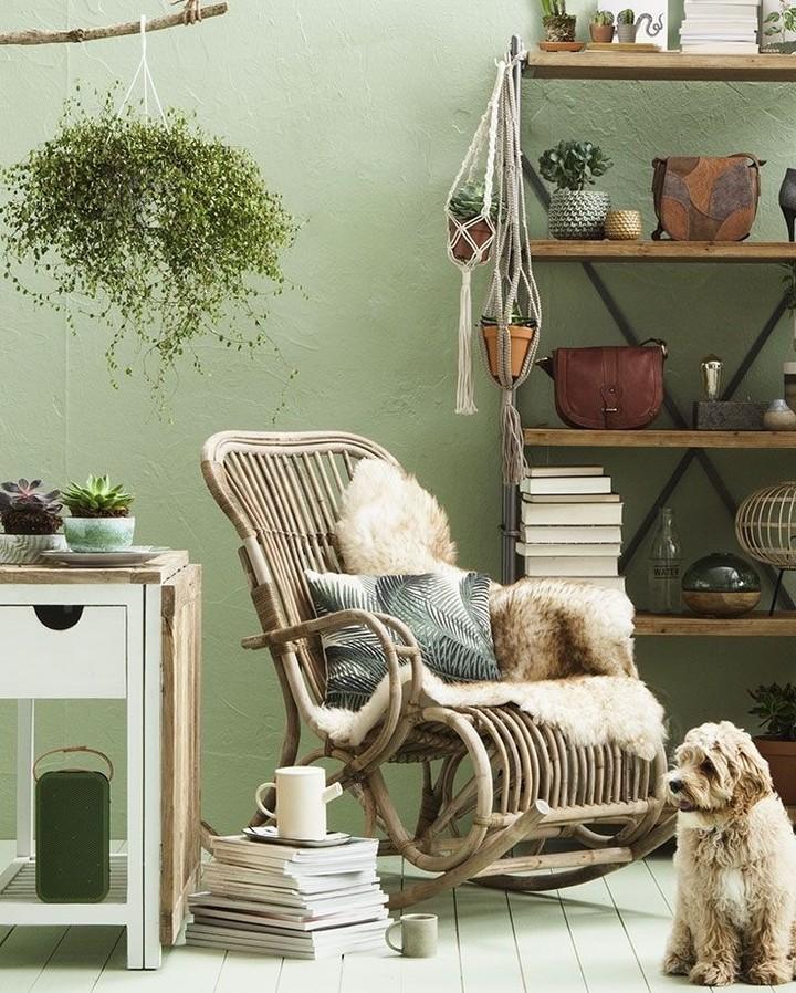 Canto de descanso com paredes verdes e cadeira de balanço de vime