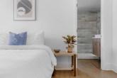 Quarto com cores claras, roupa de cama branca e mesa lateral de madeira