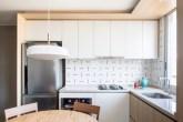 cozinha com armários brancos e azulejos estampados em apartamento pequeno