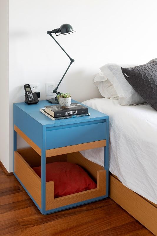 Mesa de cabeceira azul e marro, com a parte inferior com uma almofada vermelha para pets. Acima dela, dois livros, um vasinho com suculenta, uma luminária preta e um telefone sem-fio.