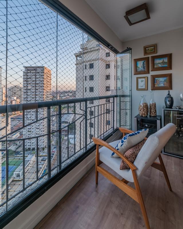 Varanda com piso de madeira, uma cadeira de madeira e estofado claro; sacada com vidro e rede de proteção