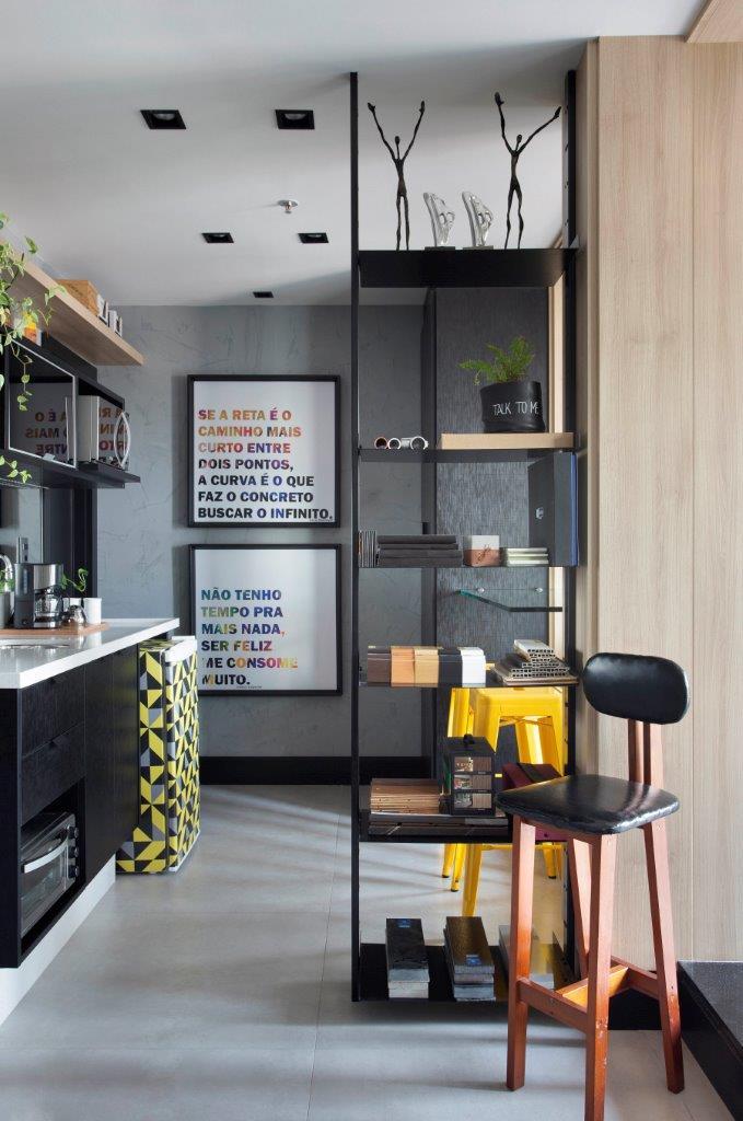 Escritório com cadeira preta à frente e bancada preta com utensílios de cozinha. Quadros com citações ao fundo