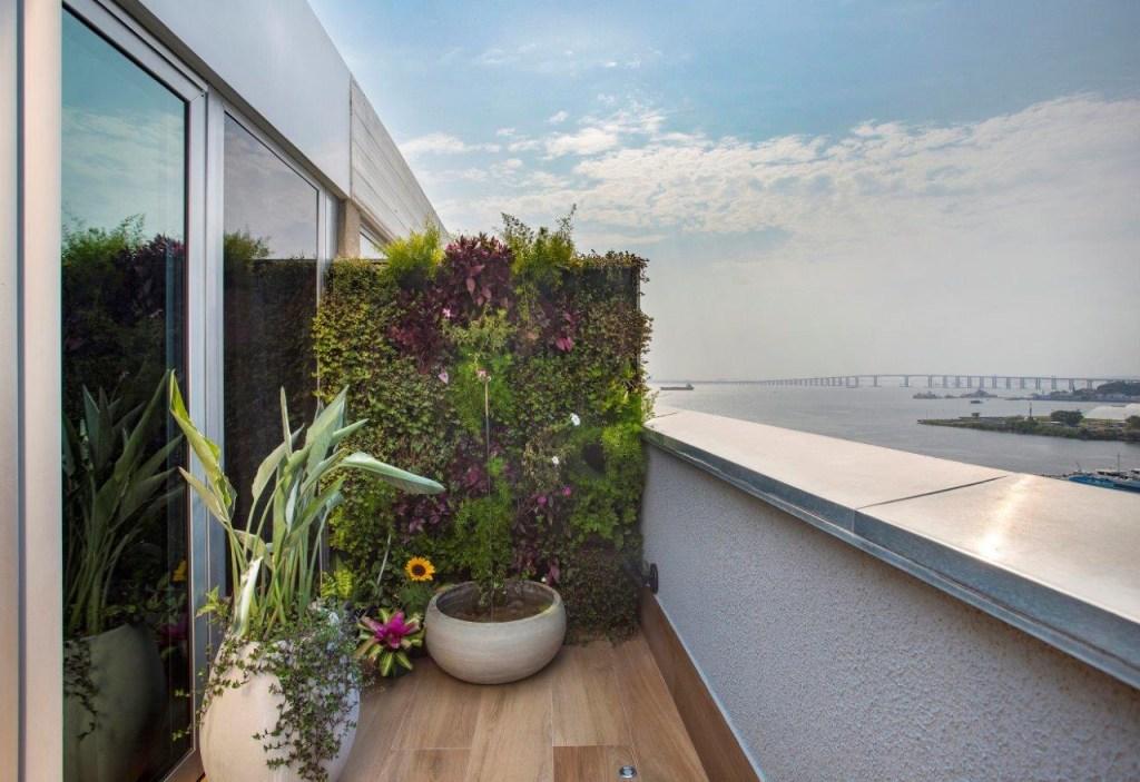 Varanda com jardim vertical. Vasos de plantas e fonte de água. Mar ao fundo.