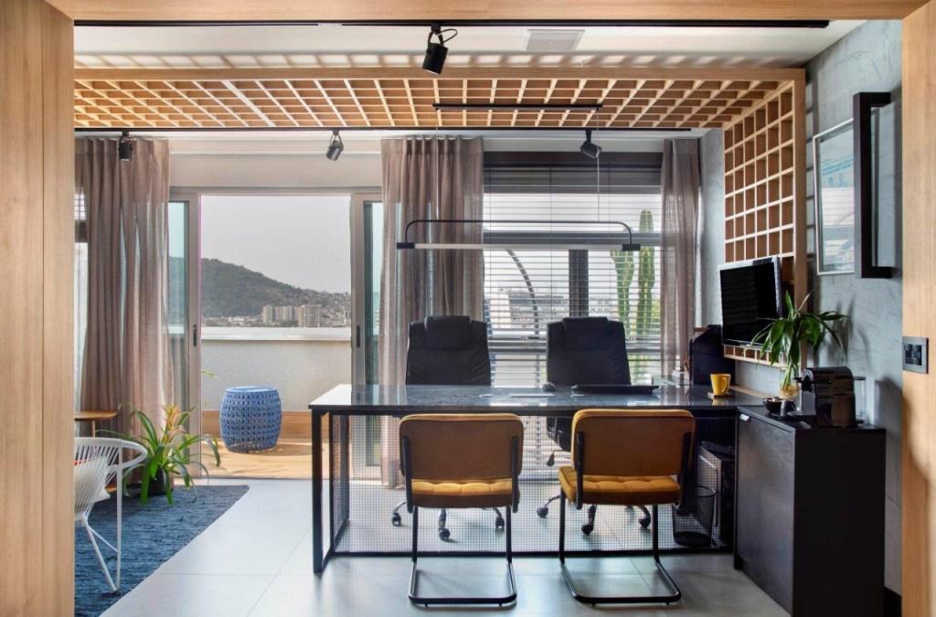 Escritório com mesa de quatro lugares. Porta para a varanda ao fundo.