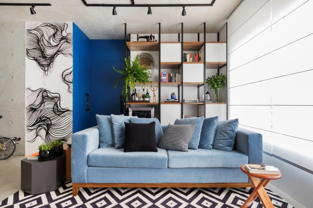 Sala de estar com sofá azul claro, tapete branco e preto geométrico. Estante vazada ao fundo. Parede em concreto aparente com porta azul.
