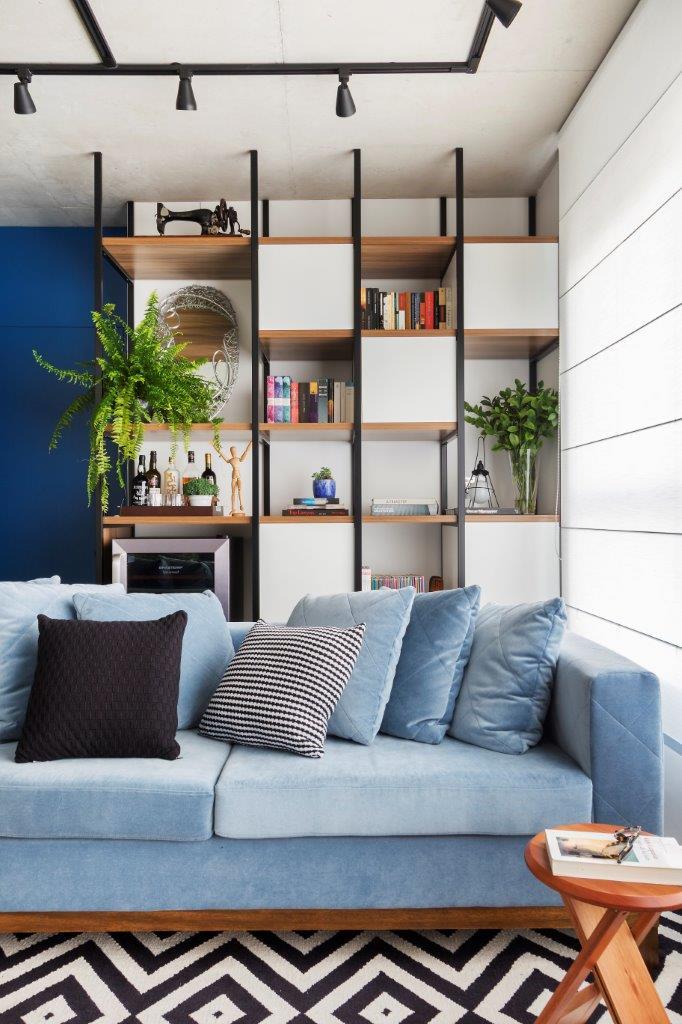 Detalhe sofá azul e estante vazada ao fundo. Nas prateleiras livros, plantas, uma adega e um boneco modulor