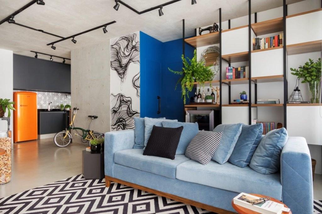 Sofá azul e estante vazada. Parede e teto de concreto aparente. Ao fundo, bicicleta encostada na parede e geladeira laranja.