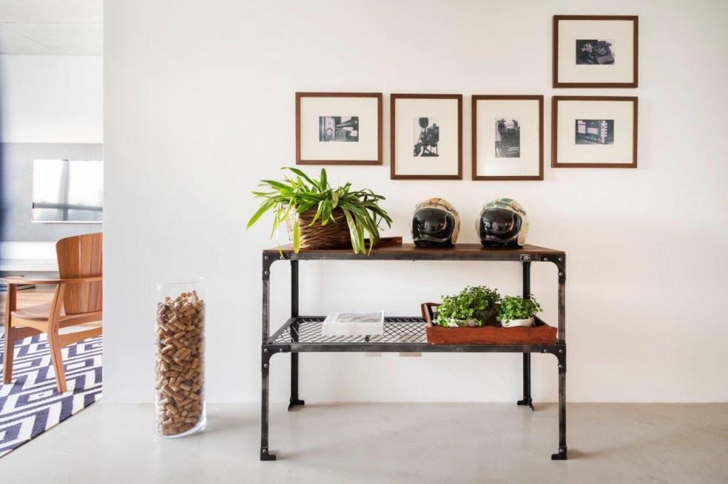 Aparador vintage encostado na parede. Um vaso de planta na prateleira superior ao lado de dois capacetes de moto. Na parede, cinco quadros com fotos