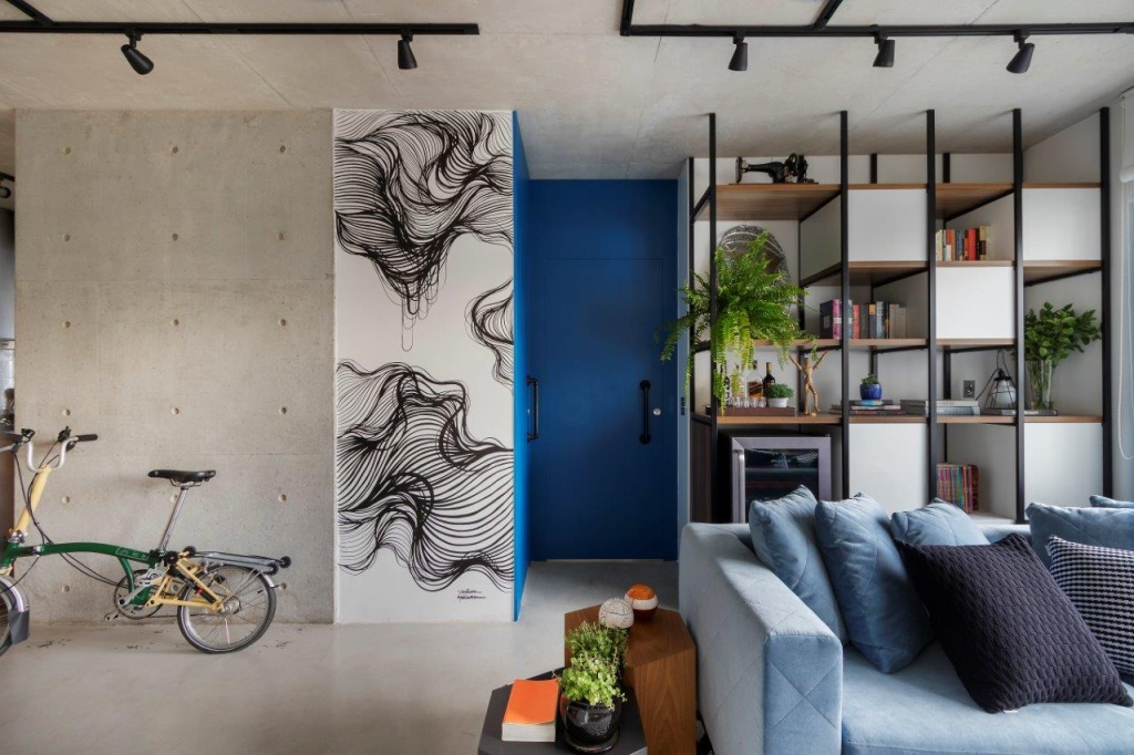 Estar com parede de concreto aparente. Bicicleta dobrável amarela encostada na parede. Obra em grafite em parte da parede. Portas azuis. Sofá à direita e estante vazada ao fundo
