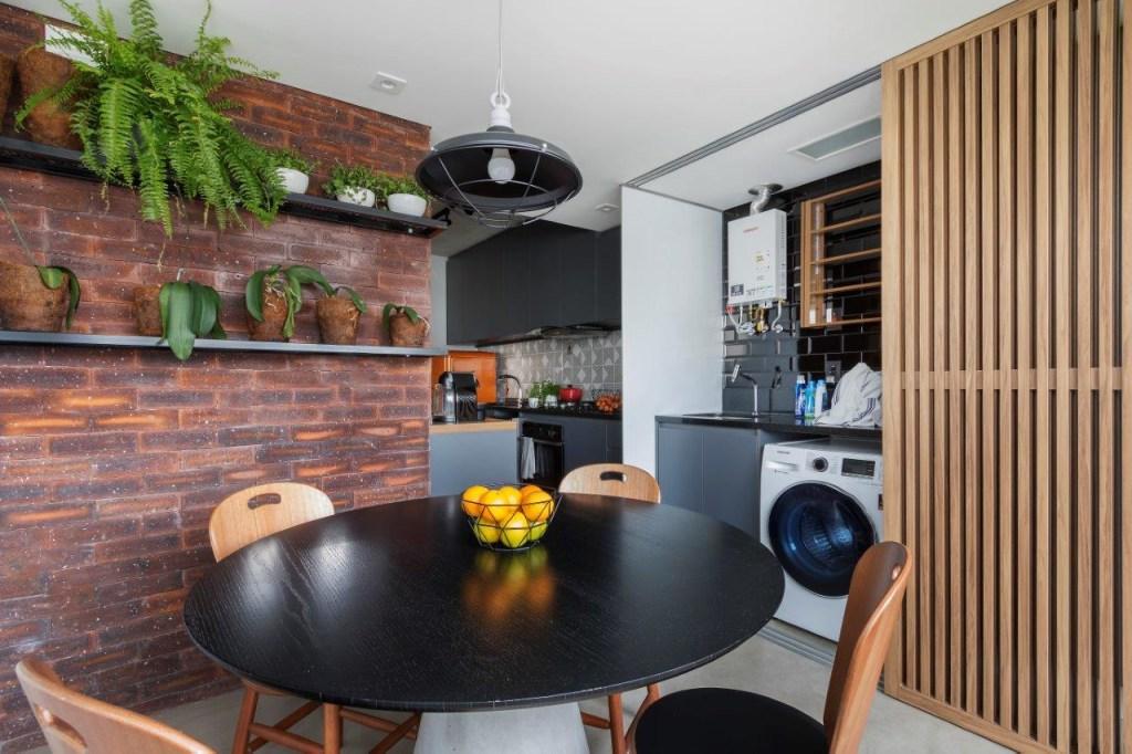 Área de receber com mesa e cadeiras em madeira. Parede de tijolos com prateleiras com vasos de plantas. Porta de madeira deslizável que abriga máquina de lavar e pia.