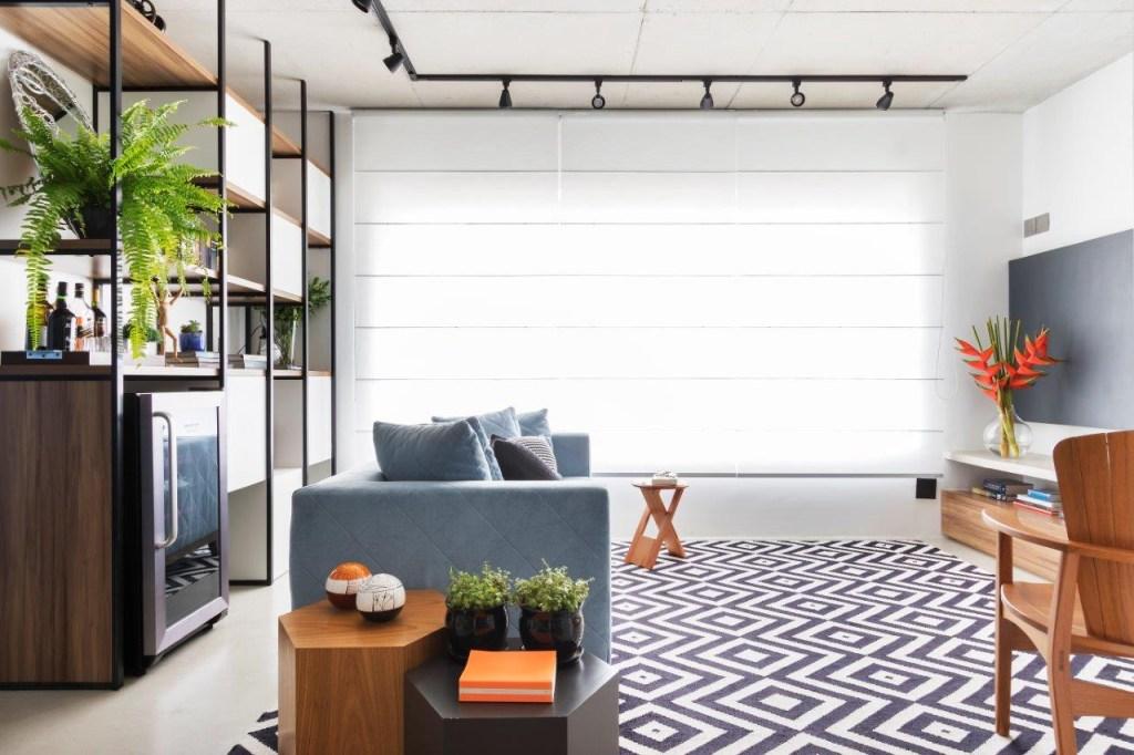 Estar na perspectiva da entrada. Sofá azul de lado, mesas de apoio hexagonais de madeira. Grande janela iluminada. Tapete geométrico branco e preto. Estante de madeira à esquerda.