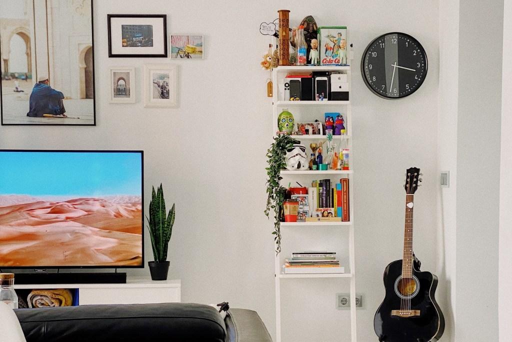 Sala de paredes brancas com quadros pendurados. Relógio de parede e violão à direita. Estante com livros, gadgets e bonecos branca no centro. Televisão no canto inferior esquerdo