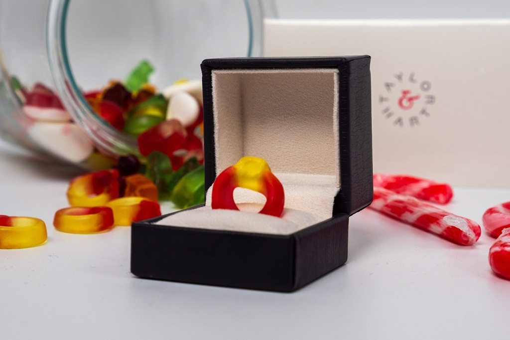 Caixa de joias preta com anel de bala de goma vermelho e amarelo. Ao fundo, balas de goma de outras cores.