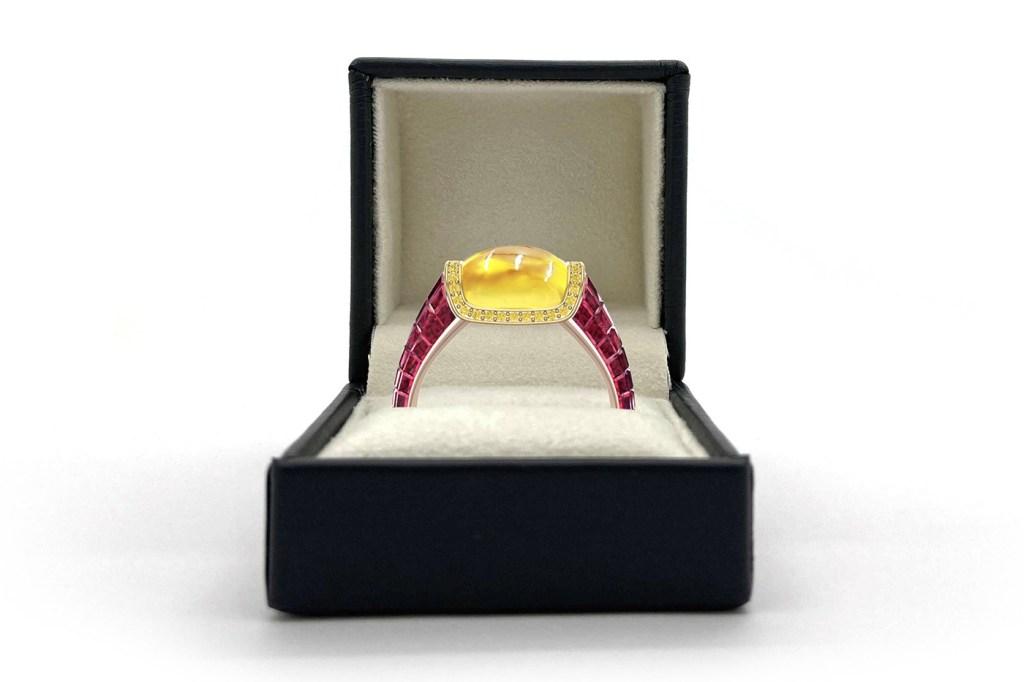 Caixa de joias preta com joia dentro. Aro com rubis e safira amarela. Safira envolta por diamantes