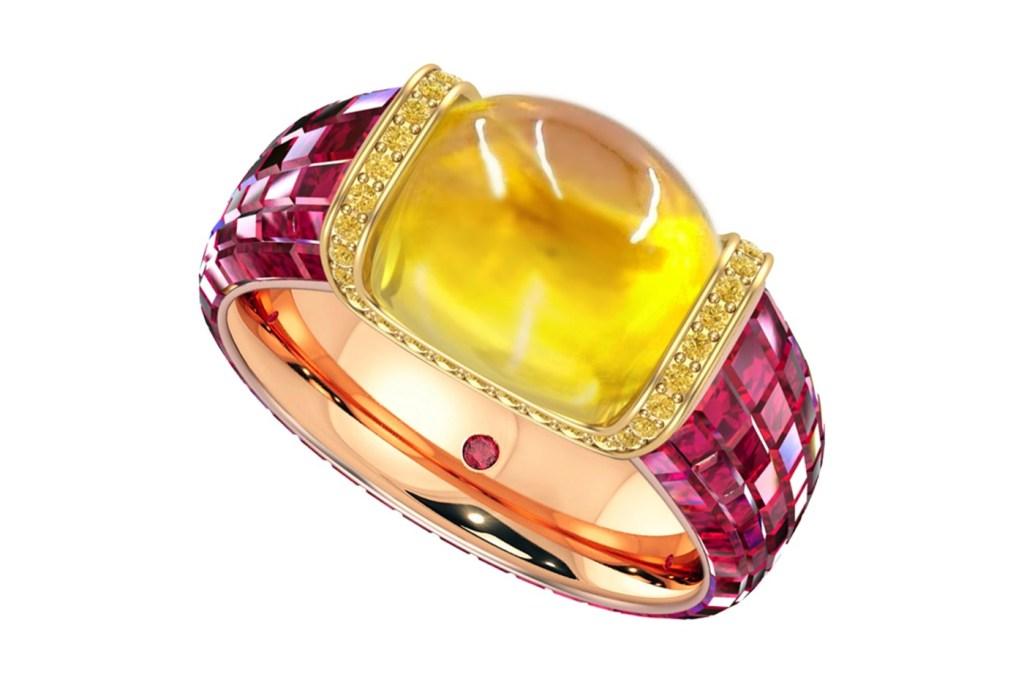 Imagem em detalhe da joia. Por baixo do aro de rubis, está uma camada de ouro rosa. Um ponto de rubi fica na parte interna do aro. Safira amarela com diamantes em volta.