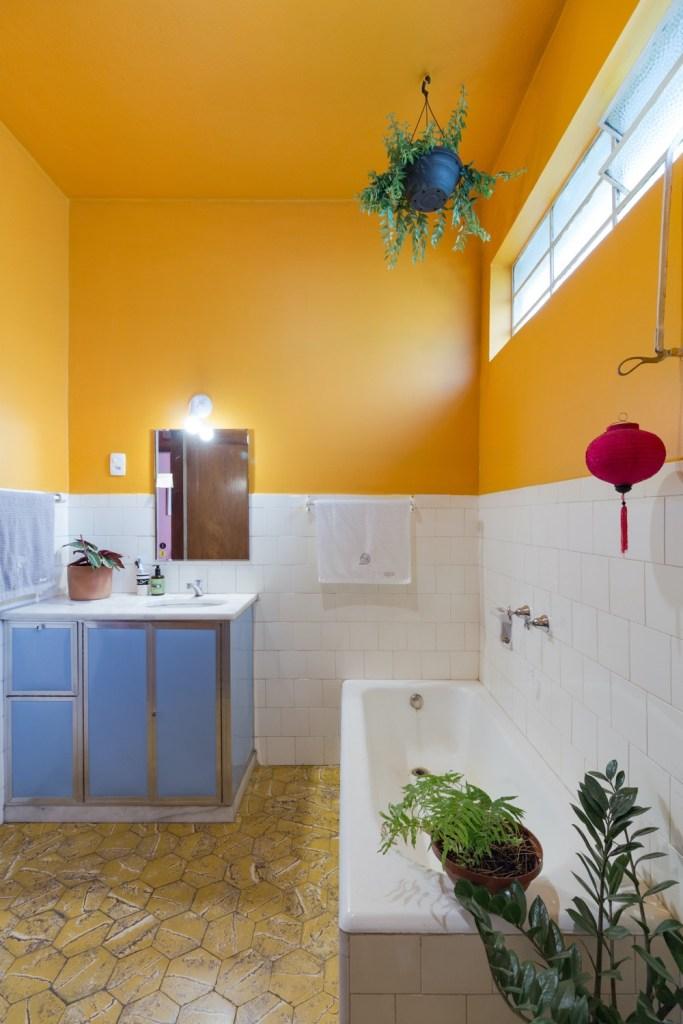 banheiro com meia parede pintada de amarelo