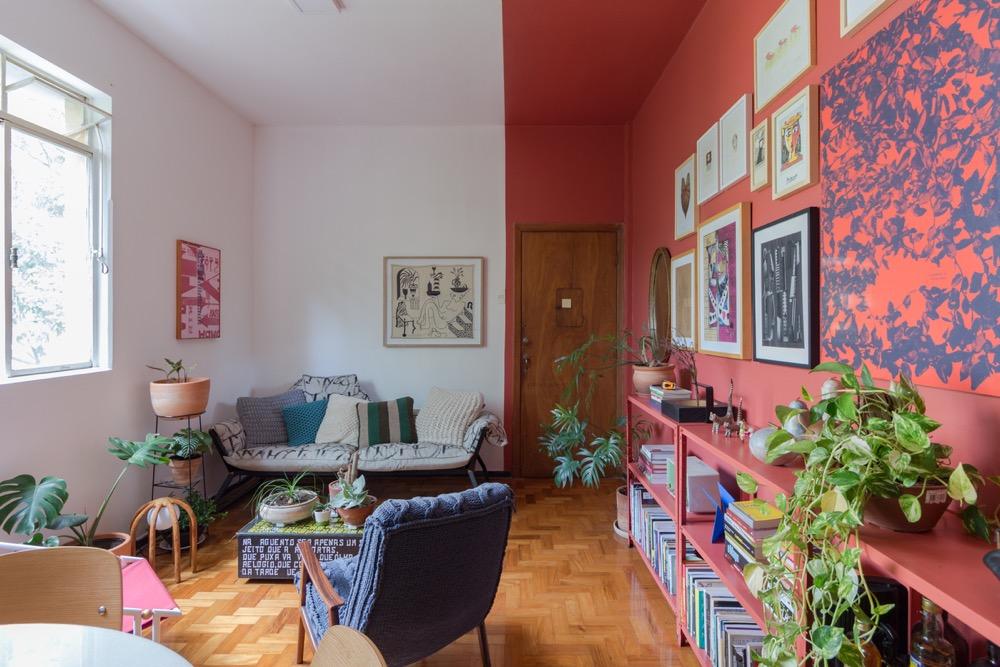 sala com parede pintada de rosa e repleta de quadros