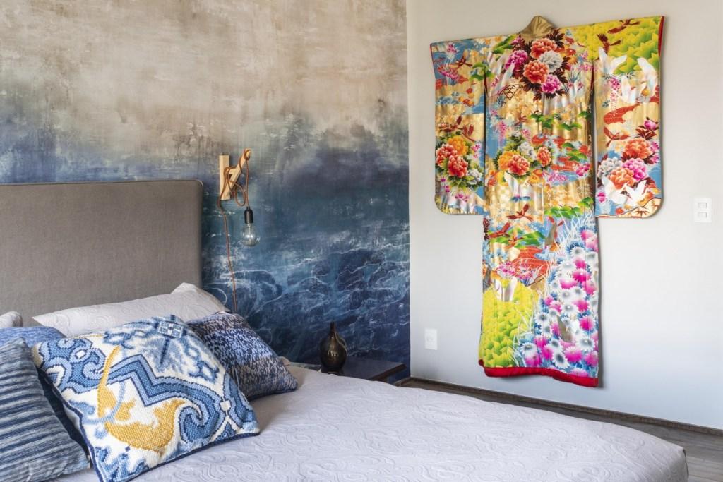 Cama com travesseiros estampados de azul e parede pintada com tons de azul a simular ondas. Um quimono colorido com flores e aves pendurado na parede.