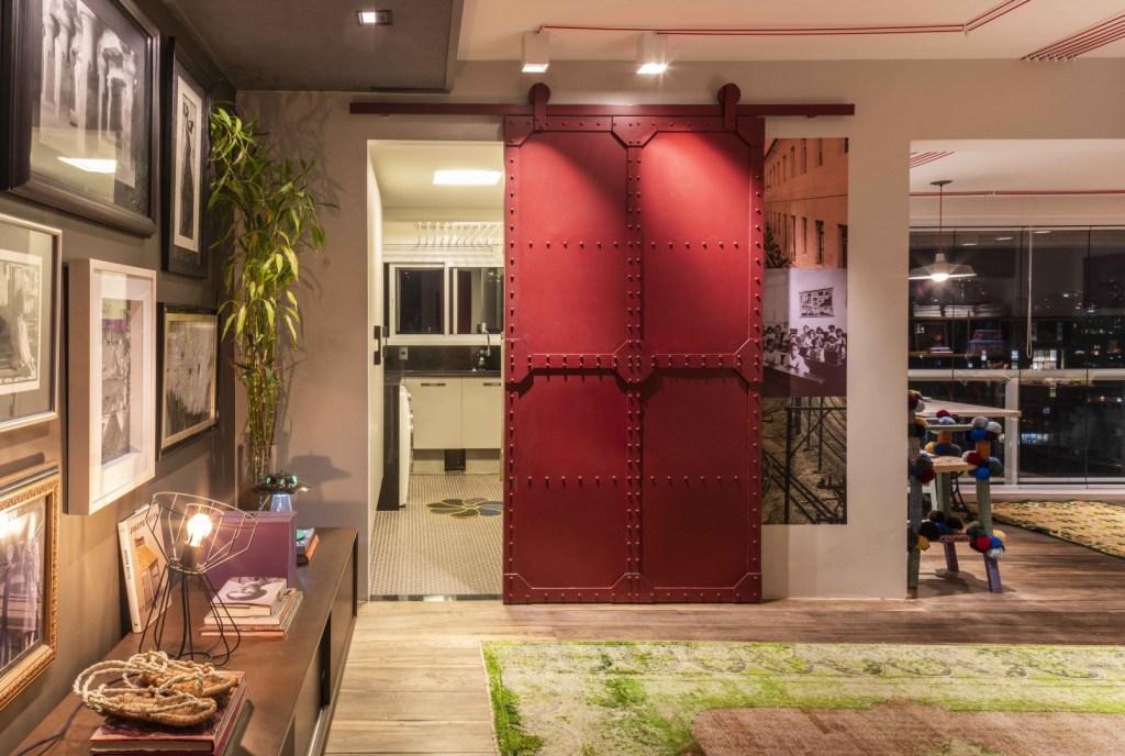 Hall de entrada com aparador e quadros. Porta vermelha de metal de deslizar aberta. Atrás da porta lavanderia com máquina de lavar e pia