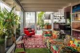 Estar com tapete vermelho sobre tapete verde. Sofá florido e poltrona vermelha. Folhagens altas na parede da esquerda. Trepadeiras ao fundo