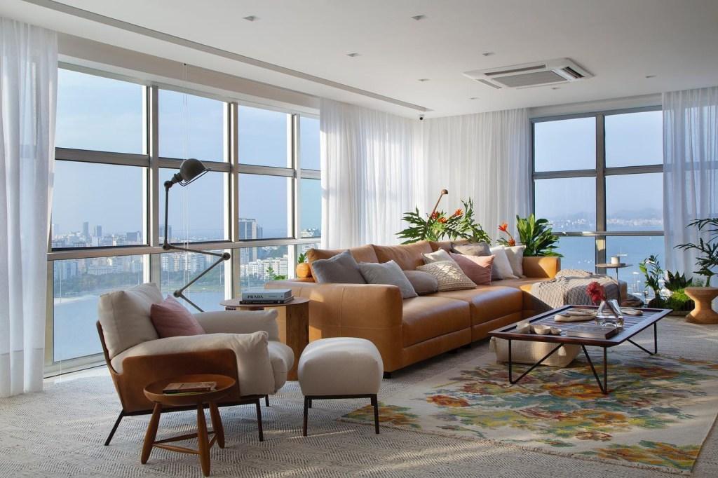 Estar com as duas paredes compostas por janelas com vista para o mar. Poltrona de madeira com estofado branco à frente e sofá de couro amarelado ao fundo. Tapete florido. Vasos com folhagens ao fundo