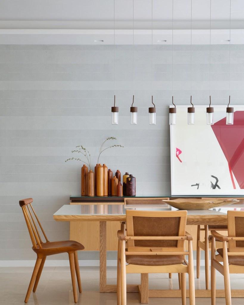 Sala de jantar com parede cinza, mesa e cadeiras em madeira. Pequenas luminárias pendem do teto. Ao fundo, um hack com quadro e vasos marrons.