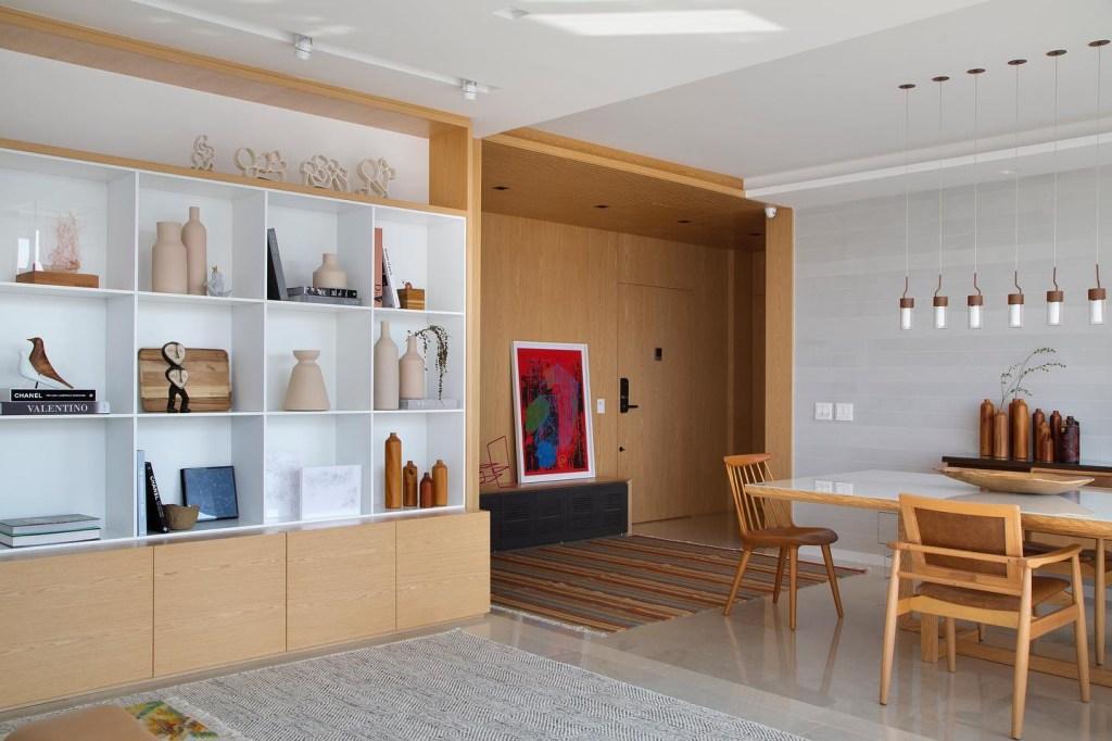 Sala com piso branco e paredes cinzas com estante em madeira com nichos brancos. Mesa de jantar e cadeiras em madeira. Hall de entrada revestido de madeira.