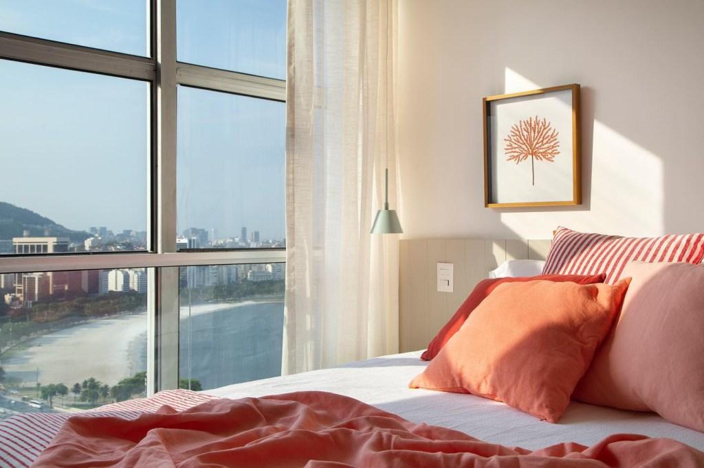 Cama com quatro travesseiros laranjas ao lado de janela com vista para a praia