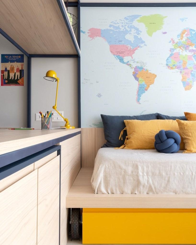 Quarto com mesa de estudos em madeira e luminária amarela. À esquerda, cama de solteiro com travesseiros amarelos e azuis. Ao fundo, mapa múndi