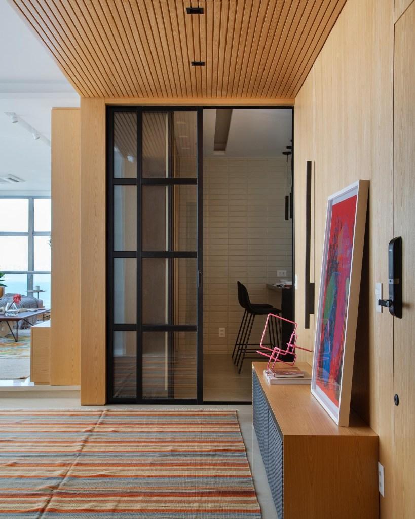 Detalhe da sala com parede e teto em madeira clara. Quadro vermelho apoiado em hack. Porta de vidro para a cozinha.