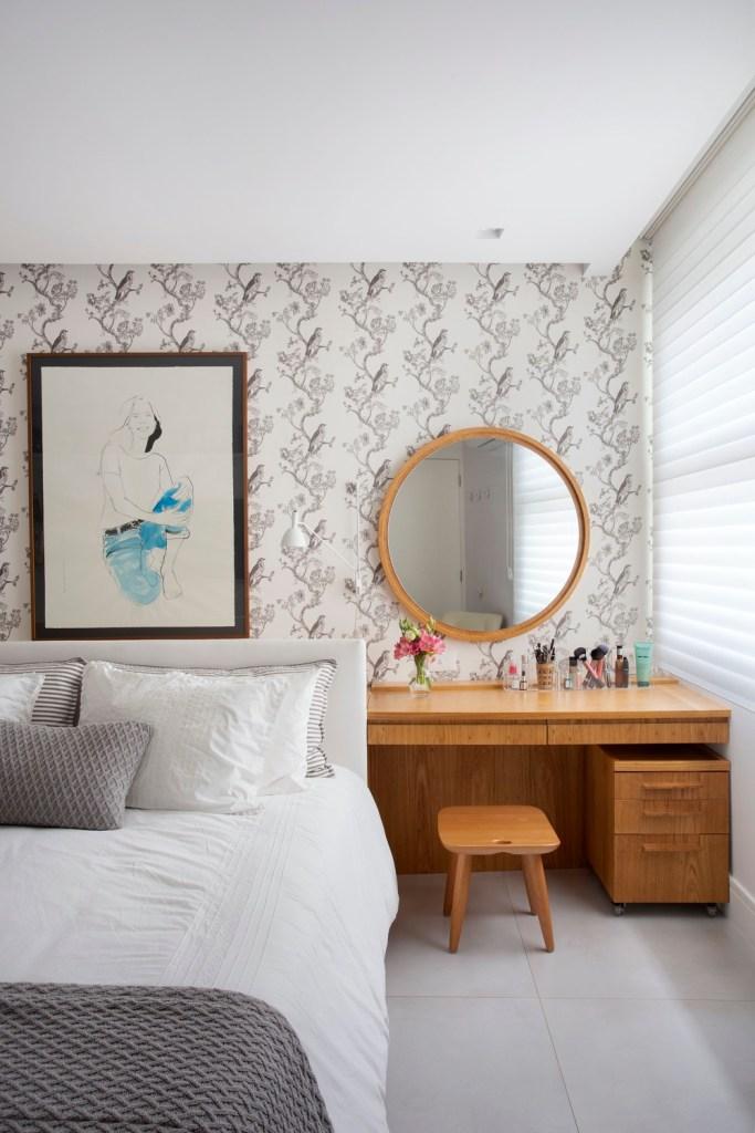 Quarto com papel de parede estampado, penteadeira e espelho redondo