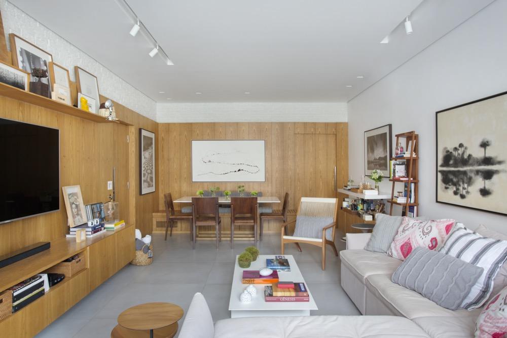 Living integrado com paredes revestidas de madeira